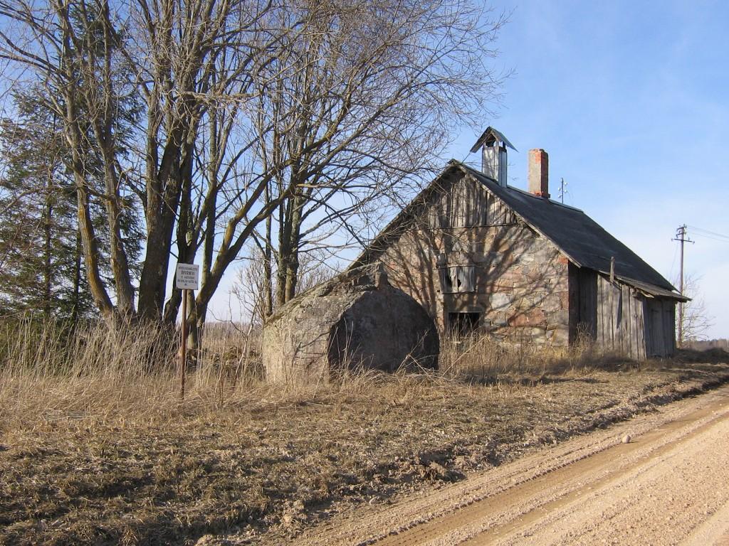 Ohvrikivi Mustajõe külas. Kõrval endine magasiait. Foto: Viktor Lõhmus, 01.04.2012.
